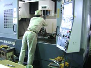 コンピューター制御の機械を熟練工が扱う
